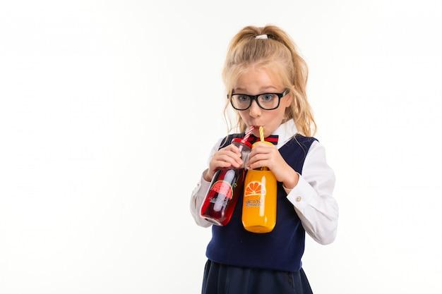 馬の尾に詰められたブロンドの髪の少女、大きな青い目、四角い黒い眼鏡のかわいい顔は、ガラス瓶のチューブにオレンジとスイカのジュースを飲みます。