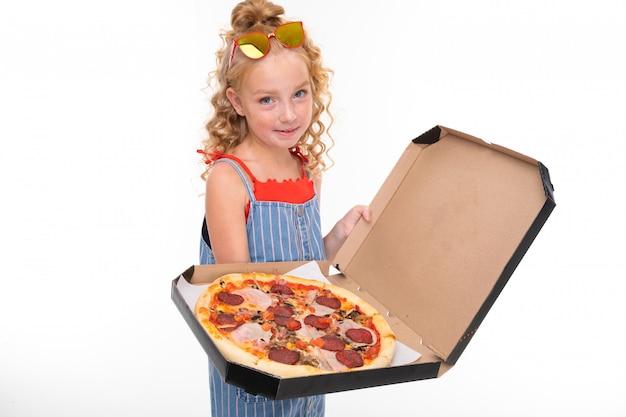 Маленькая девочка с рыжими ворсистыми волосами в красном свитере и сине-белом комбинезоне в полоску держит в коробке большую пиццу.