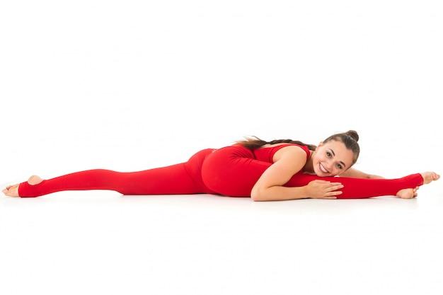 Красивая молодая гимнастка с темными длинными волосами, набитыми конским хвостом в красном спортивном эластичном костюме, сидит на шпагате