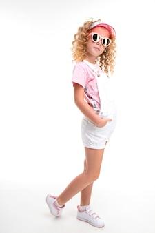 公正な赤い巻き毛、キャップ、サングラスを持つ幸せな子供は彼女の手をポケットに保持します