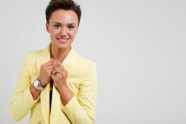 Молодая красивая девушка с короткими темными волосами, макияж и наручные часы в желтой куртке