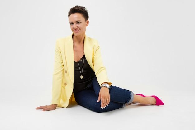 Молодая красивая девушка с короткими темными волосами, макияж и наручные часы в желтой куртке, красные лодочки сидит на полу