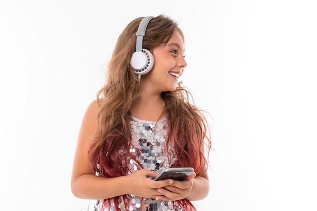 Девочка-подросток с длинными светлыми волосами, окрашенными в розовые кончики, в блестящем легком платье, стоя с наушниками и держа телефон в руке