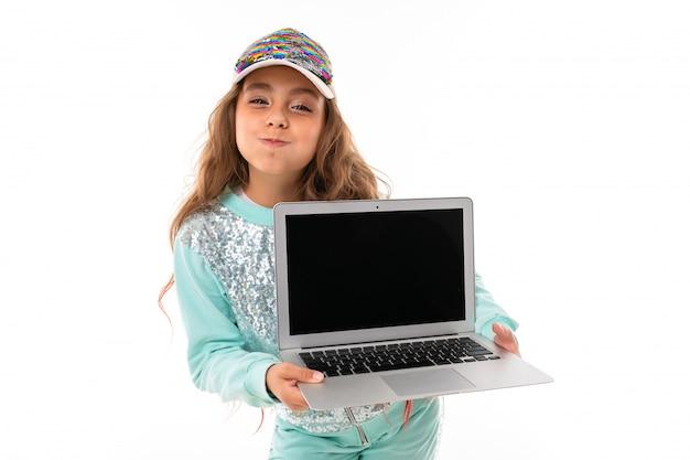 Девочка-подросток с длинными светлыми волосами, окрашенными в розовые кончики, в блестящей белой кепке, светло-голубом спортивном костюме, сумка на ремне стоит и держит ноутбук в руках