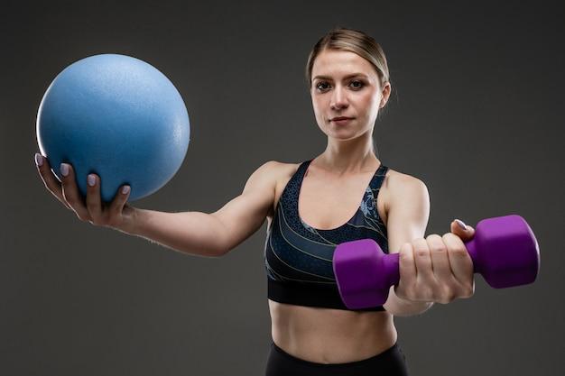 Молодая спортивная девушка с длинными светлыми волосами, запечатанными в хвост, красивой внешностью, спортивным телом, в топе и легинах, держит спортивное снаряжение, гантель и мяч