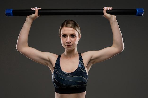 Молодая спортивная девушка с длинными светлыми волосами, покрытыми хвостом, красивой внешностью, спортивным телом, в топе и легинах, держит в руках спортивный инвентарь