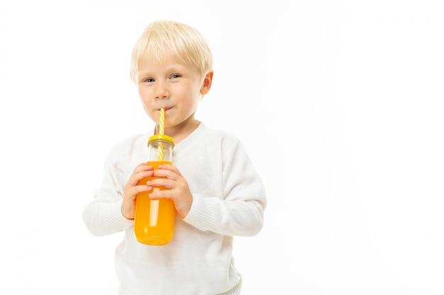 短いブロンドの髪、青い目、かわいい外観の白い男の子の男の子、水色のパンツ、スタンド、ストライプチューブ付きのガラス瓶からオレンジジュースを飲む