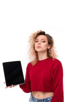 Молодая женщина с вьющимися светлыми волосами держит планшет