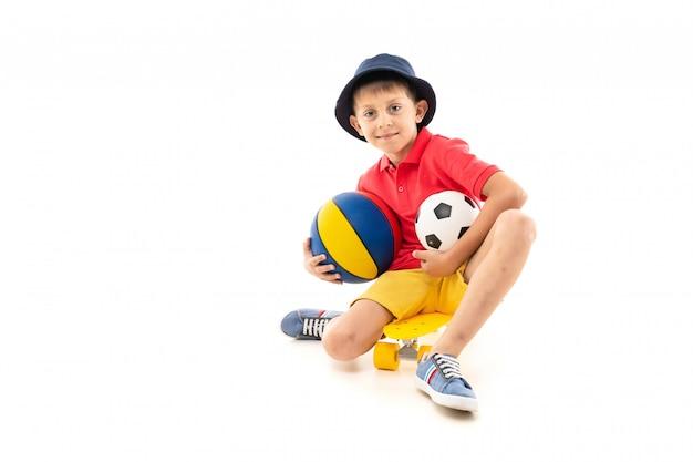 Маленький мальчик в панаме, желтая майка, красные шорты и белые кроссовки сидит на желтой копейке и держит в руке разноцветный баскетбольный мяч, футбольный черно-белый мяч и телефон
