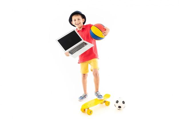 Маленький мальчик в панаме, желтой майке, красных шортах и белых кроссовках стоит на желтой копейке с баскетбольными и футбольными мячами и ноутбуком