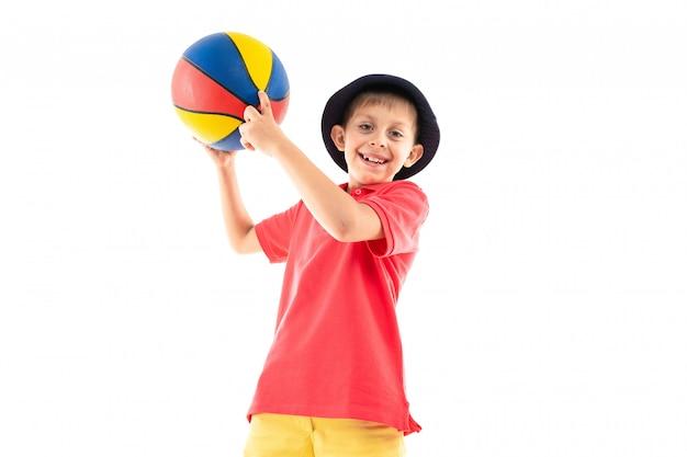 Маленький мальчик в панаме, желтой майке, красных шортах и белых кроссовках стоит с баскетбольным мячом