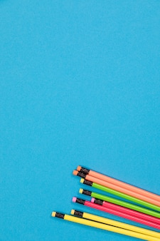 Половина видимых красочных карандашей, лежащих на лазурной поверхности
