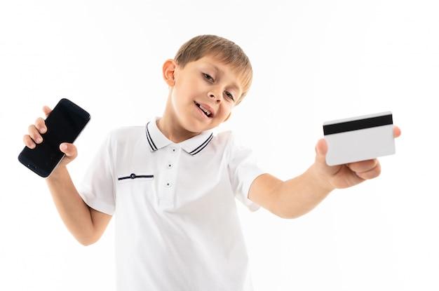 白いシャツの小さな男の子、ブロンドの髪の青いショートパンツ、電話とカードの黒いメガネが笑っています。