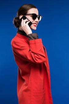 彼女の手の電話で赤い口紅を持つ女性