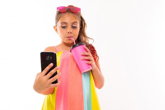 Изображение кавказской девушки с очками и телефоном пьет кофе или сок и общается со своими друзьями или семьей
