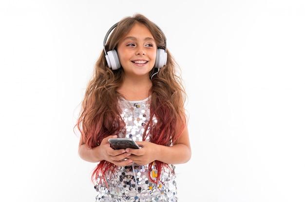 音楽を聴くと分離された黒いスマートフォンを保持している大きな白いイヤホンの輝くドレスの女の子