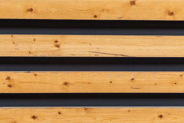 暗い表面に対して隙間のある明るい木製の板で覆われた表面