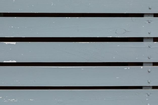 少しぼろぼろの灰色塗装の隙間のある木製の壁