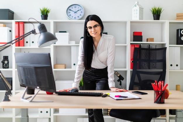 若い女の子がコンピューターの机のそばに立ち、両手を置いています。少女の隣には書類とマーカーがあります。
