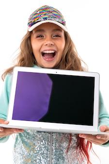 スタイリッシュな赤ちゃんが手にノートパソコンの画面を持ち、歯を大きく広げて笑顔を見せています。