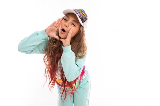 Девочка-подросток в сверкающей одежде и модной кепке кричит что-то руками возле рта