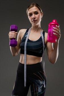 Молодая спортивная женщина с длинными светлыми волосами, набитыми в хвост, красивой внешностью, спортивным телом, в черном топе, держит на шее спортивную бутылку с водой, телефон и дюймовую ленту