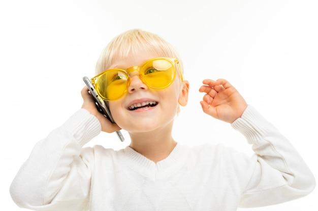 電話で楽しいチャット、笑っている黄色のメガネで白い表面の少年