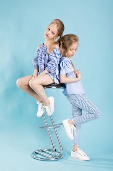 Девочки-близняшки в голубых одеждах позируют возле барного стула на синем