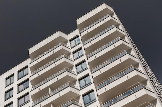 バルコニーと窓、嵐の雨の日に暗い空の表面を備えたモダンで豪華なアパートの地上斜めビュー