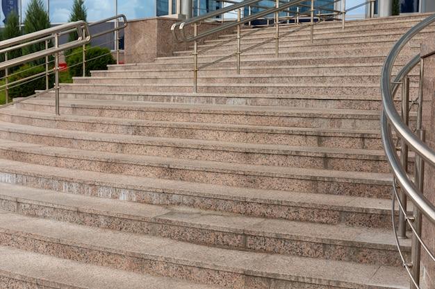 ステンレスの手すりが付いているコンクリートのタイル張りの階段の地上ビュー