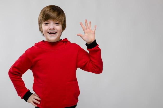灰色の開いたやしを示す赤いセーターのかわいい自信を持って白人少年