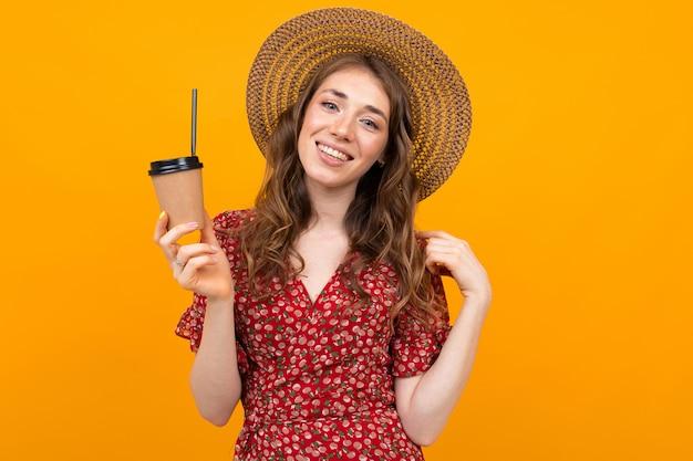コーヒーのグラスと帽子の黄色い表面にスタイリッシュな女の子