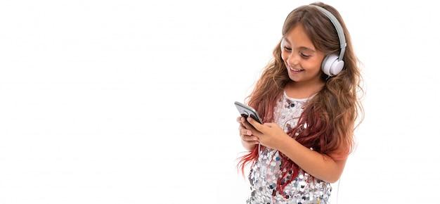 大きな白いイヤホンが音楽を聴くと分離された黒いスマートフォンの画面を見つめて、輝くドレスの女の子のパノラマ