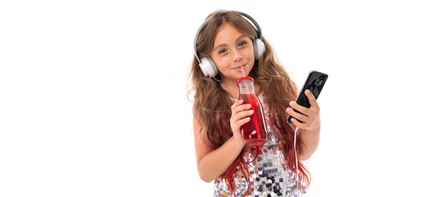 音楽を聴く大きな白いイヤホン、黒いスマートフォンを押しながら分離されたプラスチック製のボトルから赤い飲み物をすすり輝くドレスの女の子