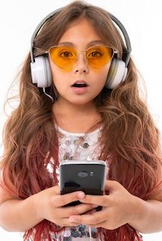 Удивленная девушка в желтых очках, с большими наушниками держит черный смартфон