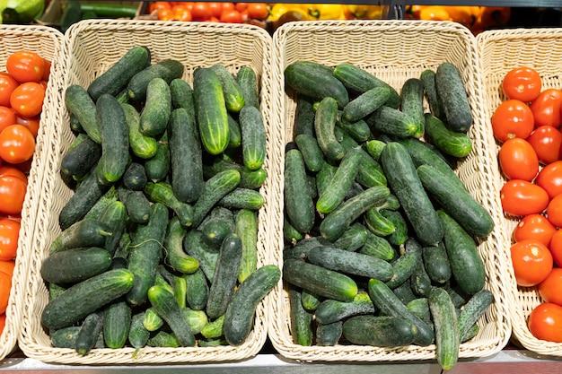 Зеленые домашние огурцы и красные спелые помидоры в плетеных корзинах в супермаркете