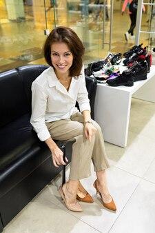 Девушка сидит на кожаном диване, примеряет и выбирает туфли на высоком каблуке в магазине.