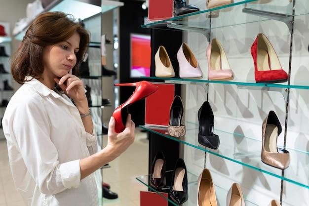 Обдуманная молодая женщина выбирает красные лодочки на высоких каблуках в торговом центре.