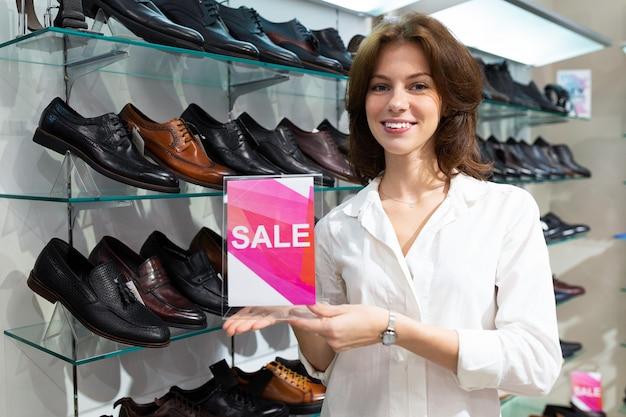 Молодая женщина улыбается и держит планшет с продажи знак в магазине с сапогами мужчин