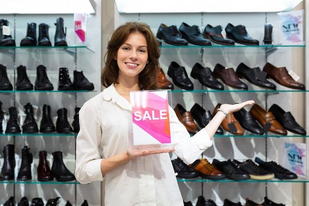 Молодая женщина демонстрирует скидки в отделе мужской обуви.