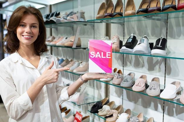 Молодая женщина держит таблетку с знаком продажи и указывает на нее в магазине против женской обуви