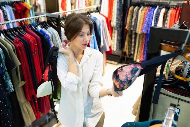 短い髪を持つ若い笑顔の女性は美しいベルトバッグを選びます。