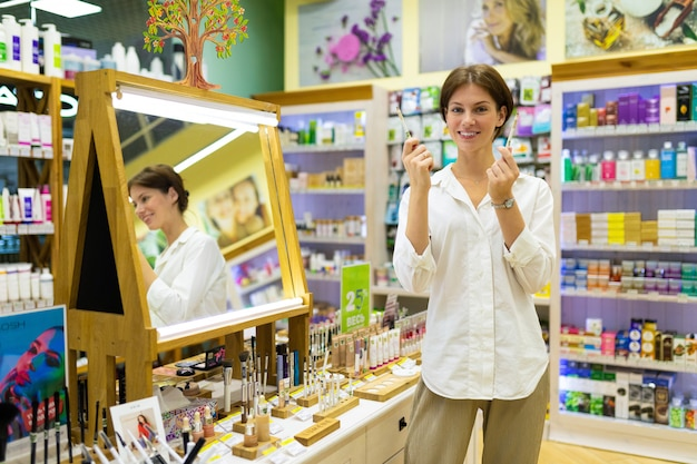 暗い短い髪の少女は、化粧品店でアイペンシルとアイブロウペンシルを選びます。