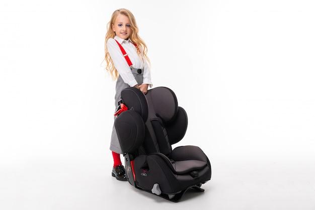 化粧と白いシャツ、赤いプルアップ、檻の中のパンツ、赤い靴下、赤ちゃんの椅子と靴でブロンドの髪を持つ少女。