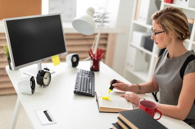 若い女の子が彼女の手に黄色のマーカーを持って、オフィスのテーブルに座っています。少女の前には本が開いています。
