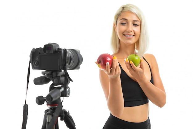 公正な髪を持つスポーティな少女は、黒のスポーツトピックと黒のレギンスでカメラの前に赤と緑のリンゴを置きます。