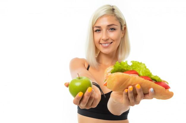黒のスポーツトップと黒のレギンスにブロンドの髪を持つ若いスポーツ少女は、青リンゴとサンドイッチを保持しています。
