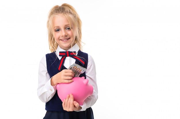 ブロンドの髪を持つ少女の写真はピンクのブタの貯金箱と白い背景で隔離の笑顔を保持しています。