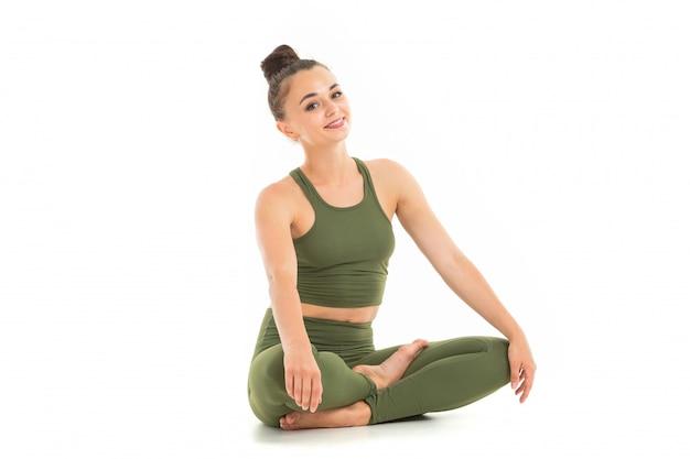 Красивая молодая гимнастка с темными длинными волосами, сшитая в пучок в зеленом спортивном эластичном костюме, сидит и улыбается.