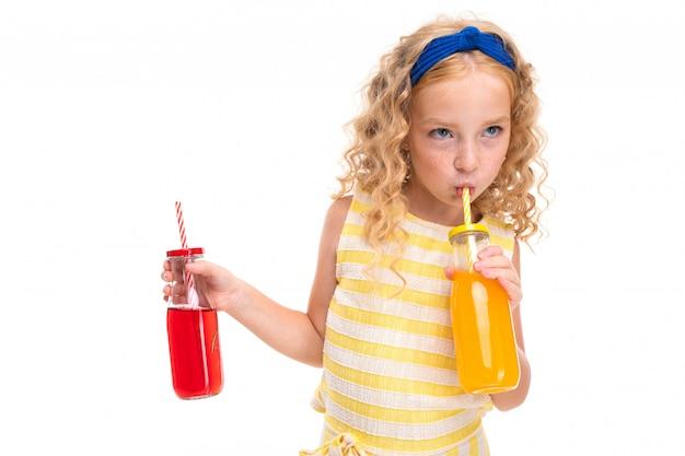 白と黄色の縞模様の夏のスーツに赤い毛の髪の少女、頭に青い包帯を巻いたものは、ガラス瓶のパイプでオレンジジュースを飲み、スイカジュースを保管しています。